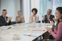 Lächelnde Geschäftsleute klatschen im Konferenzraum — Stockfoto