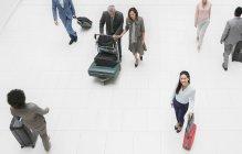 Високий кут портрет усміхнений бізнесжінка з валізою в аеропорт — стокове фото