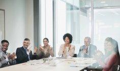 Счастливые, поддерживающие бизнесмены хлопают в конференц-зале — стоковое фото