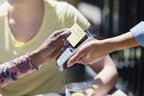 Жінка платять офіціанткою з смарт-карти — стокове фото
