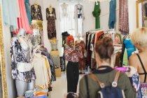 Молоді жінки друзі з камери покупки телефону в магазині одягу — стокове фото