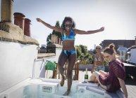 Amis jeunes femmes insouciantes en bikinis au bain bouillonnant sur le toit — Photo de stock