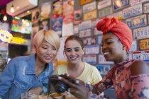 Jovens amigas usando câmera digital no bar — Fotografia de Stock