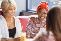 Щасливі молоді жінки друзі пили коктейлі, мова йде в ресторан — стокове фото