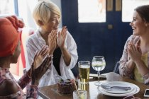 Счастливые молодые подруги празднуют день рождения в ресторане — стоковое фото