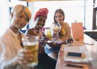 Портрет улыбающейся, уверенной в себе молодой женщины друзья тост коктейли в баре — стоковое фото