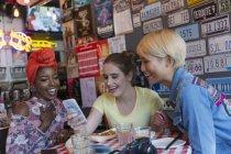 Молоді жінки друзі, використовуючи смарт-телефону в м. бар — стокове фото
