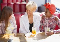 Young women friends talking and drinking cocktails in sunny restaurant — Stock Photo