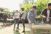 Masculino amigos aproveitando churrasco no ensolarado verão quintal — Fotografia de Stock