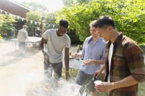 Young men barbecuing in sunny backyard — Foto stock