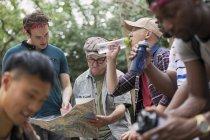 Grupo dos homens com mapa e garrafas de água caminhadas na floresta — Fotografia de Stock