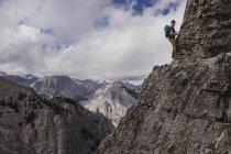 Uomo montagna arrampicata ripida, parete di montagna scoscesa — Foto stock