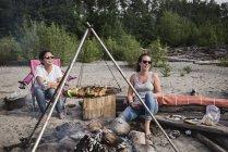 Mulheres relaxantes, desfrutando de churrasco na praia — Fotografia de Stock