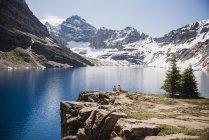Пара сидит на скале с видом на спокойные, солнечные горы и озеро, парк Йохо, Британская Колумбия, Канада — стоковое фото