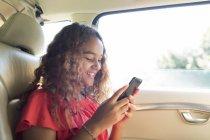 Lächeln zwischen Mädchen mit Smartphone auf dem Rücksitz des Autos — Stockfoto