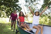 Bonne mère et ses filles poussant le canot dans les bois — Photo de stock