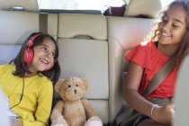 Sœurs heureuses et ours en peluche sur le siège arrière de la voiture — Photo de stock