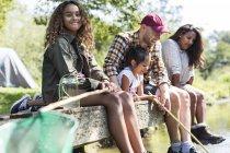 Ritratto sorridente ragazza pesca con la famiglia sul molo — Foto stock
