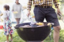 Man barbecuing hamburgers at campsite — Stock Photo