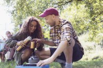 Daughter pouring coffee from insulated drink container for father at camping stove — Stock Photo