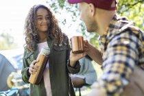 Figlia versando caffè dal contenitore di bevande isolate per padre al campeggio — Foto stock