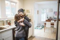 Affectionate mother and daughter hugging in kitchen — Stock Photo