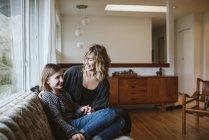 Мать и дочь сидят на диване в гостиной — стоковое фото