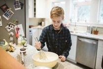 Tween boy baking in kitchen — Stock Photo