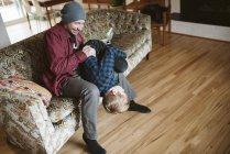 Père ludique tenant son fils à l'envers sur le canapé du salon — Photo de stock