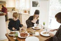 Семейный завтрак за кухонным столом — стоковое фото