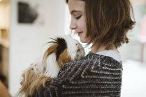 Девушка держит милую длинноволосую морскую свинью — стоковое фото