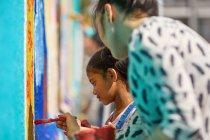 Profesora y alumna de primaria pintando en la pared - foto de stock