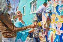 Community volunteers painting vibrant mural on sunny urban wall — Stock Photo