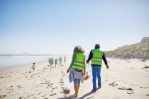 Volunteers cleaning up litter on sunny, sandy beach — Stock Photo