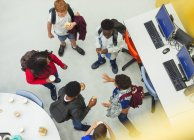 Étudiants du secondaire parlant à la bibliothèque — Photo de stock