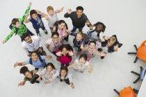 Portrait d'en haut d'élèves enthousiastes du premier cycle du secondaire et d'enseignants qui applaudissent — Photo de stock