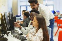 Вчитель допомагає молодшим студентам з використанням комп'ютера в комп'ютерній лабораторії — стокове фото