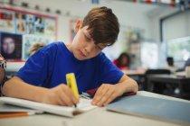 Focused junior high school student using highlighter, doing homework in classroom — Stock Photo