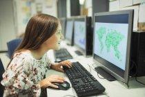 Neugierige Realschülerin schaut im Klassenzimmer auf Landkarte am Computer — Stockfoto