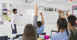 Молодші Учні середньої школи з піднятими руками під час уроку у класі — стокове фото