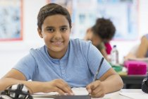 Portrait confident junior high school boy student doing homework in classroom — Stock Photo