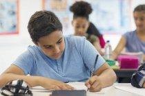 Junior high school boy student doing homework in classroom — Stock Photo