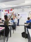 Männlicher Lehrer leitet Unterricht an Projektionswand im Klassenzimmer — Stockfoto