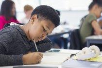 Gymnasiast macht Hausaufgaben im Klassenzimmer — Stockfoto