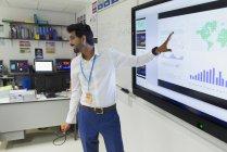 Enseignant masculin menant la leçon à l'écran en classe — Photo de stock