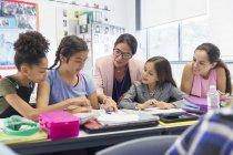 Вчителька і старшокласники навчаються за столом у класі. — стокове фото