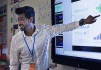 Lächelnder männlicher Lehrer leitet Unterricht am Touchscreen im Klassenzimmer — Stockfoto