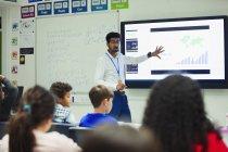 Professeur masculin à l'écran tactile principale leçon en classe — Photo de stock