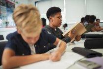 Junior high school boy opening notebook at desk in classroom — Stock Photo