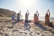 Gruppe übt Yoga am sonnigen Strand während Yoga Retreat — Stockfoto